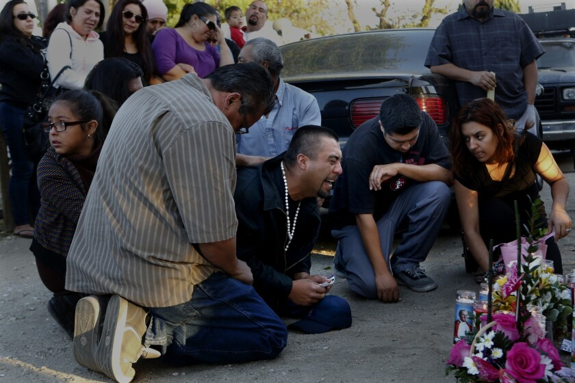 Rudy Coronado, center, the father of the slain girls, is comforted during a vigil.