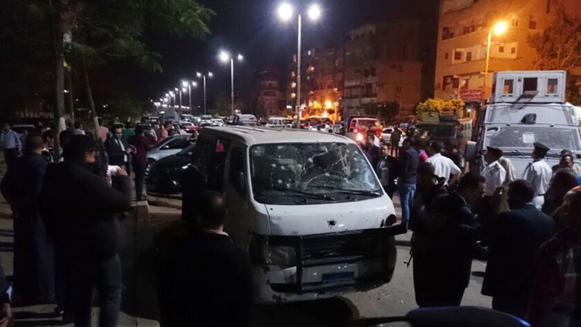 Egyptian police and civilians gather around a bullet ridden microbus in the south Cairo neighborhood of Helwan.