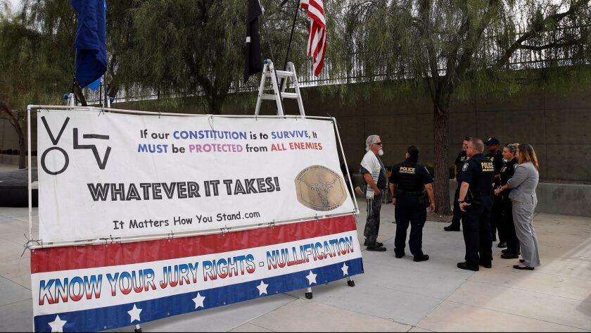Police officers talk to a supporter of Nevada rancher Cliven Bundy outside federal court in Las Vegas last month.