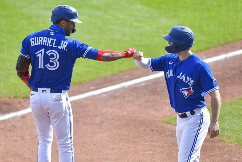 Toronto Blue Jays' Lourdes Gurriel Jr., left, and Randal Grichuk, right, celebrate after scoring on Gurriel Jr.'s two-run home run against the New York Mets during the second inning of a baseball game in Buffalo, N.Y., Sunday, Sept. 13, 2020. (AP Photo/Adrian Kraus)