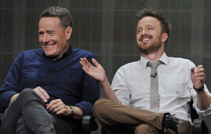 """Bryan Cranston, left, and Aaron Paul, cast members in the television series """"Breaking Bad,"""" share a laugh onstage during AMC's Summer 2013 TCA press tour at The Beverly Hilton Hotel on Friday, July 26, 2013, in Beverly Hills, Calif."""