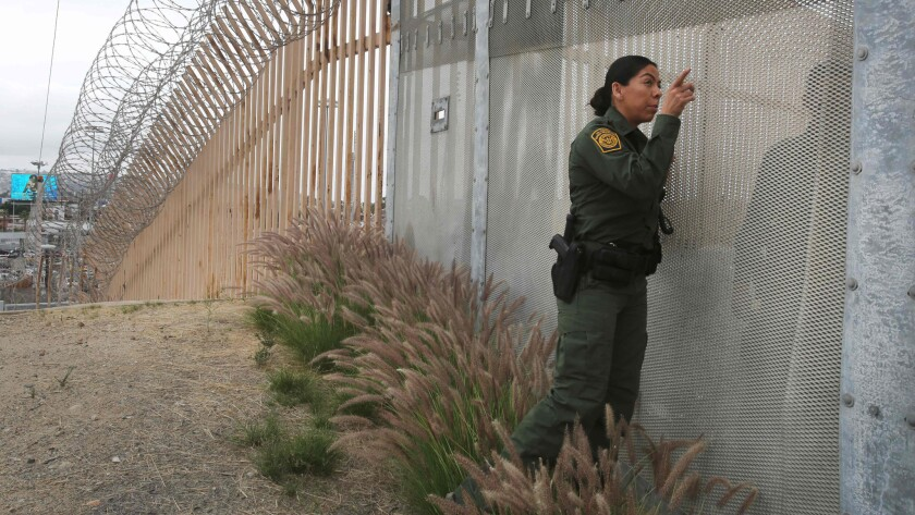 A Border Patrol agent talks with another agent through a fence at the U.S.-Mexico border in San Diego, California.