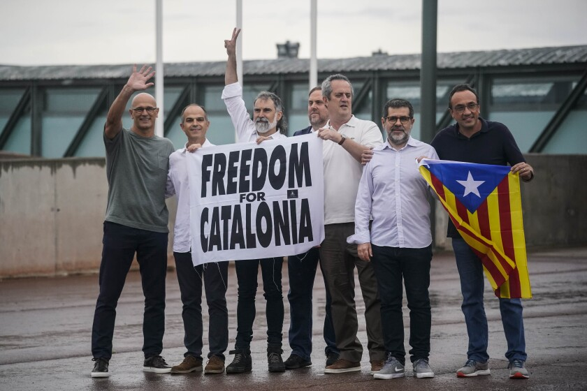 """Catalan leaders imprisoned for their role in the 2017 push for an independent Catalan republic, hold a banner and an """"estelada"""" or Catalan pro-independence flag outside Lledoners prison in Sant Joan de Vilatorrada, near Barcelona, Spain, Wednesday, June 23, 2021. Nine separatists pardoned by the Spanish government are expected to leave the prisons where they were serving lengthy terms for organizing a bid for an independent northeastern Catalonia region nearly four years ago. Spain's official gazette published earlier in the day the government decree pardoning them. (AP Photo/Joan Mateu)"""