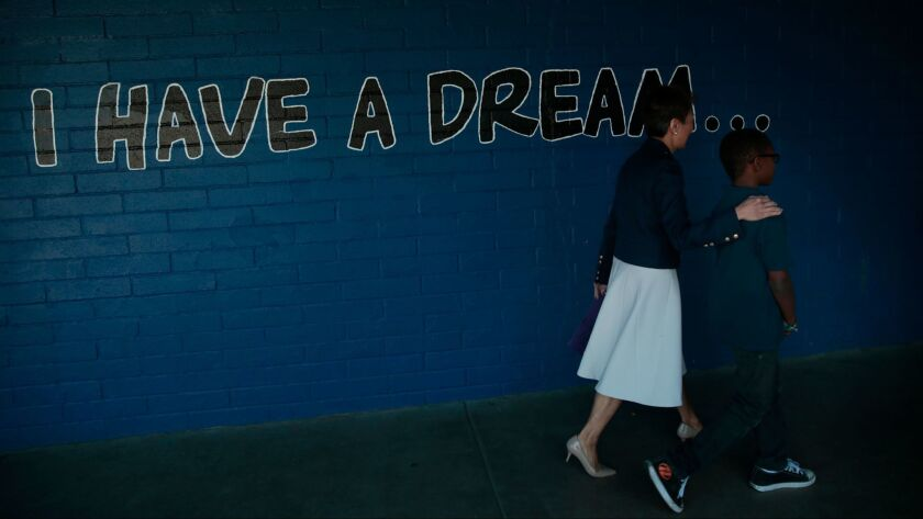 Jane Chu, chairwoman of the National Endowment for the Arts, is escorted by fourth-grader Jamiah Walker, 10, through the halls of Martin Luther King Jr. Elementary School in Compton.