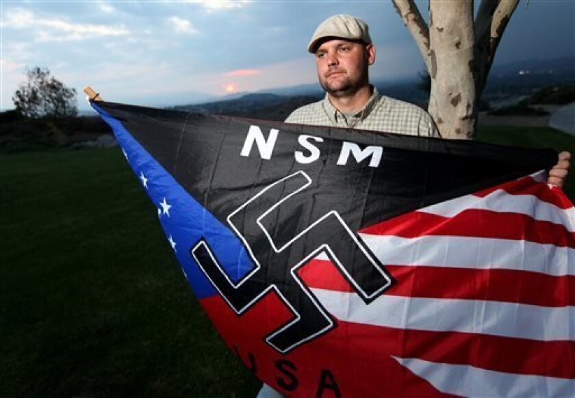 FILE - In this Oct. 22, 2010 file photo, Jeff Hall, who was killed by his son, holds a Neo Nazi flag while standing at Sycamore Highlands Park near his home in Riverside, Calif. On Friday Oct. 25, 2013 a judge will to determine where Hall's son will spend his teens and, possibly, his early adult ye