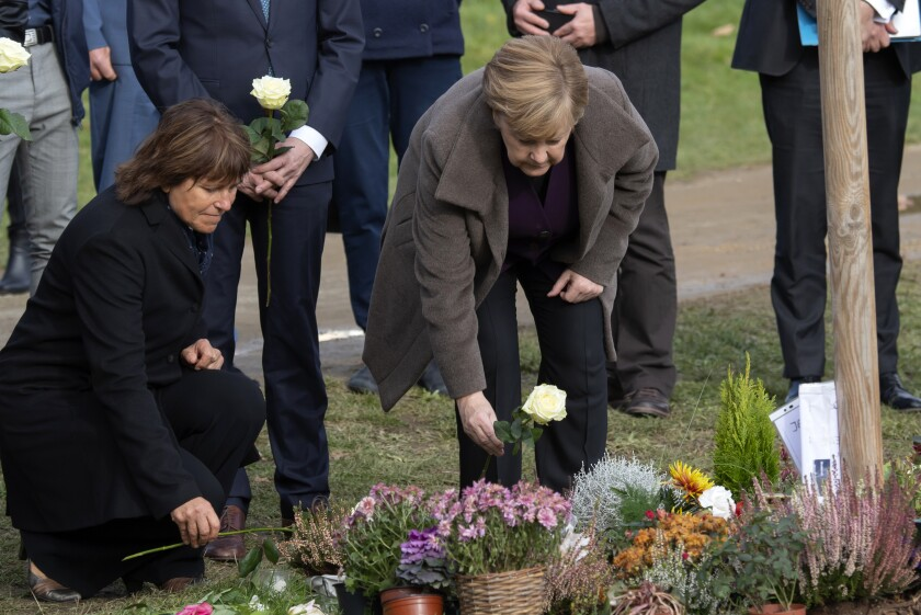 German Chancellor Angela Merkel, right, lays down flowers besides Pia Findeiss, Zwickau's Lord of Mayor, left, at the memorial place and freshly planted trees for the victims of the neo-Nazi 'Nationalist Socialist Underground' NSU in Zwickau, eastern Germany, Monday, Nov. 4, 2019. The city of Zwickau planted 10 new trees for all victims of the NSU with the help of donations at the memorial site. The cell calling itself the National Socialist Underground allegedly targeted migrants, killing 10 people between 2000 and 2007. (AP Photo/Jens Meyer)