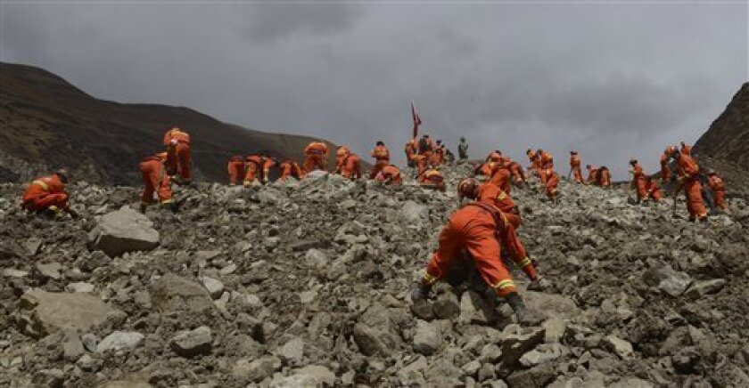 In this March 30, 2013 photo provided by China's Xinhua News Agency, rescue workers conduct search and rescue work at the site where a large-scale landslide hit a mining area in Maizhokunggar County of Lhasa, southwest China's Tibet Autonomous Region. Emergency crews in Tibet slogged through pileup