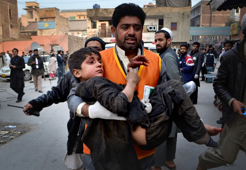 An injured child is carried away after an explosion at an auto repair shop in Peshawar, Pakistan.