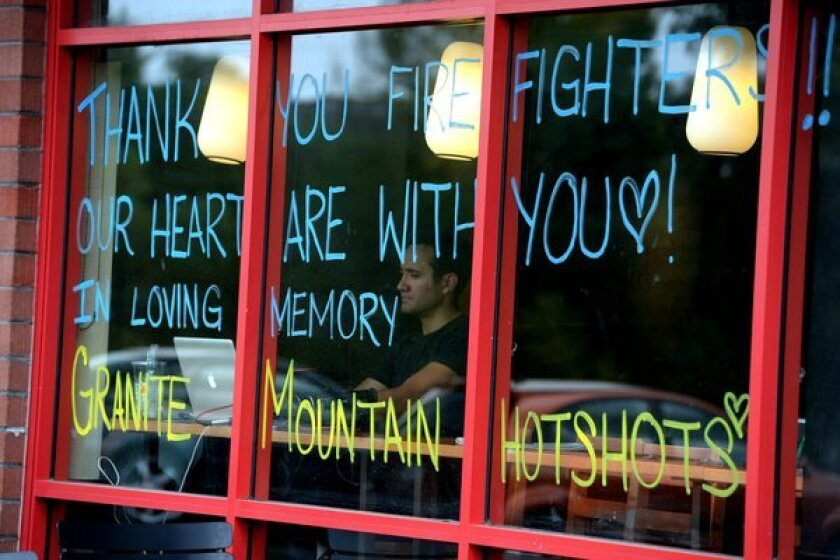 """Writing on a restaurant window in Prescott, Ariz., reads, """"Thank You Firefighters!! Our Hearts are with you. In Loving Memory. Granite Mountain Hotshots."""""""