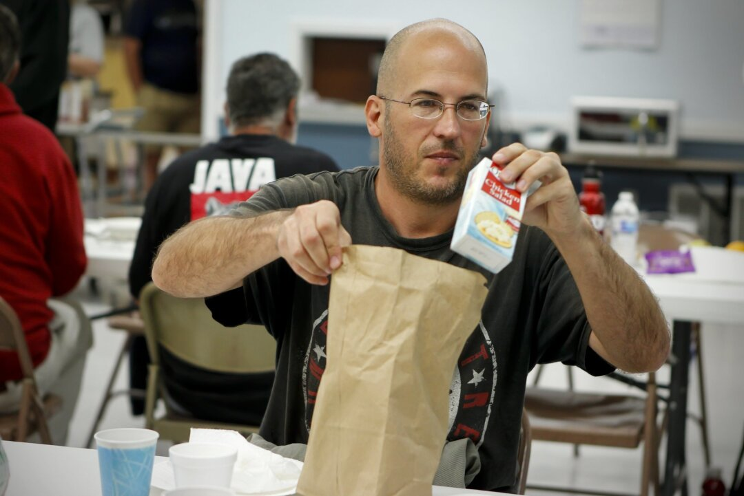 Larry Tucholski, 43, checks out a lunch bag received at the Wesley United Methodist Church on El Cajon on Thursday, Oct. 24, 2013. Tucholski is among those whose food stamp, or CalFresh, benefits will go down in November.
