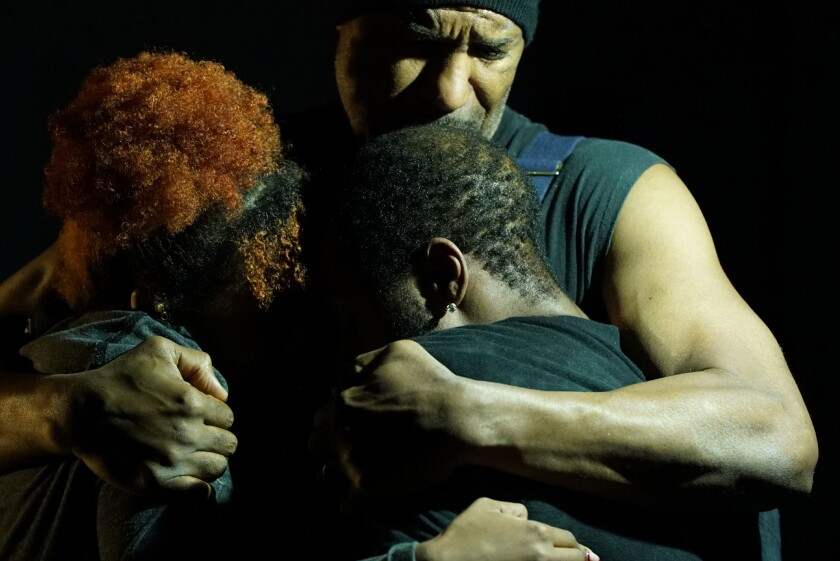 A man holds two people in a tight embrace.