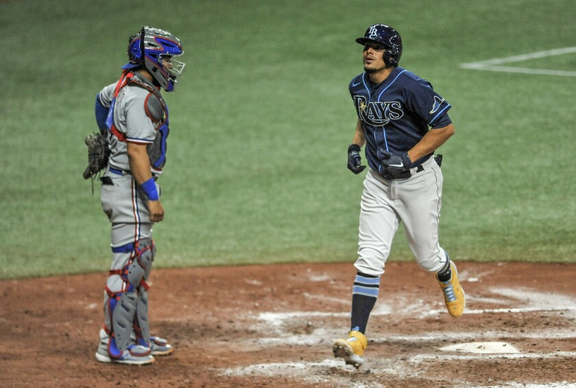 Texas Rangers catcher Jose Trevino watches as Tampa Bay Rays' Willy Adames, right, scores on a solo home run off Rangers Taylor Hearn during the eighth inning of a baseball game Monday, April 12, 2021, in St. Petersburg, Fla. (AP Photo/Steve Nesius)
