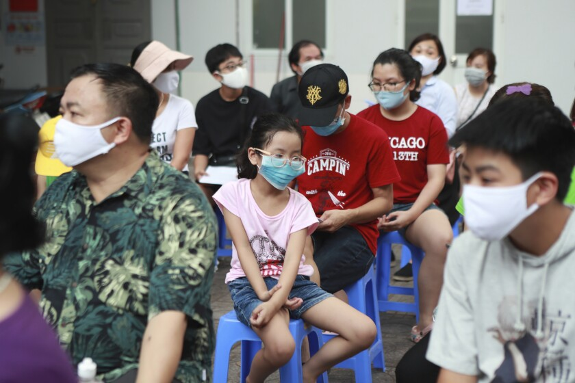 People wait in line to be tested for COVID-19 in Hanoi, Vietnam