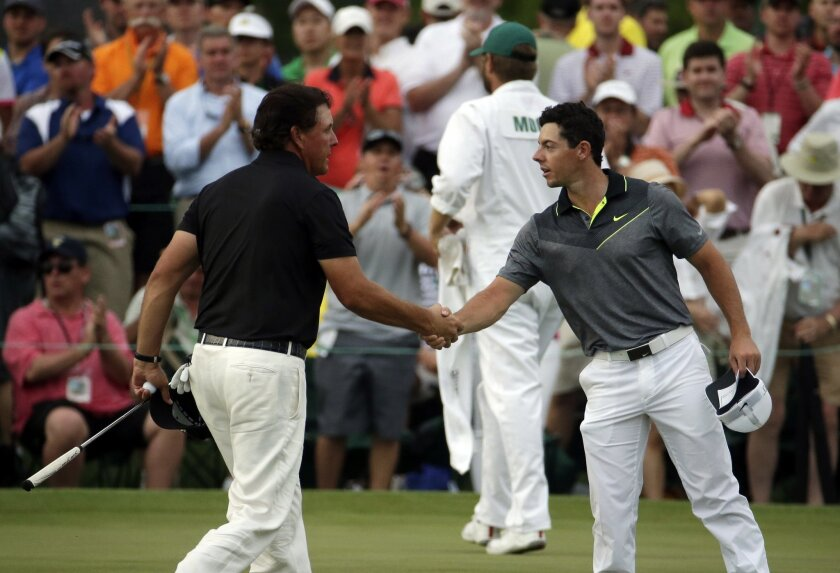 Phil Mickelson, left, shakes hands with Rory McIlroy, of Northern Ireland, during the second round of the Masters golf tournament Friday, April 10, 2015, in Augusta, Ga. (AP Photo/Charlie Riedel)