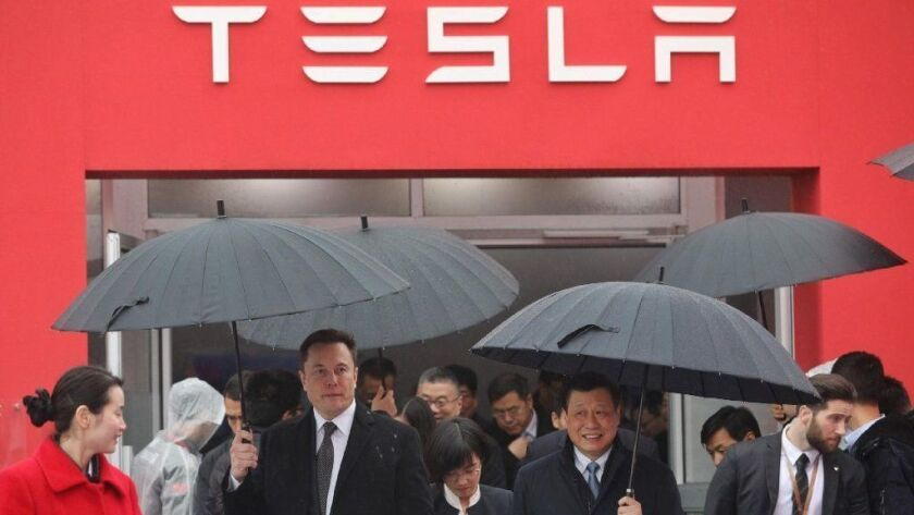 Tesla boss Elon Musk, left, walks with Shanghai Mayor Ying Yong during the Jan. 7, 2019, groundbreaking ceremony for a Tesla factory in Shanghai. The factory will allow the electric-car manufacturer to dodge the China-U.S. tariff crossfire.