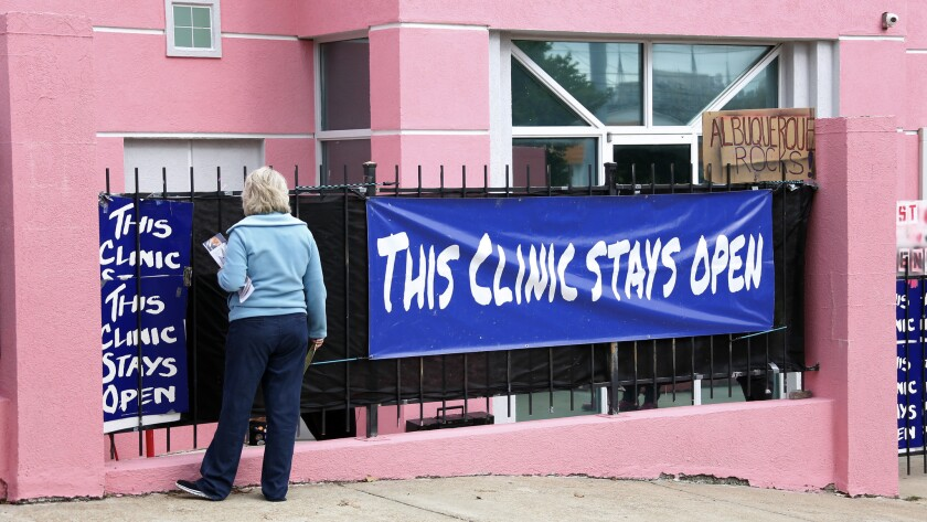 Antiabortion protester Mary McLaurin calls out to a patient from behind a sign outside the Jackson Women's Health Organization clinic in Jackson, Miss.