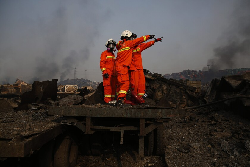 Firemen wearing gas masks search the explosion area in the port city of Tianjin, China.