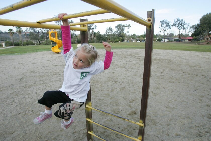 Norah Dahlkamp, 3, swung on the bars at Lake Murray Community Park in San Diego on Tuesday. Norah's mother has formed a group called the Lake Murray Playground Project that is trying to renovate the playground.