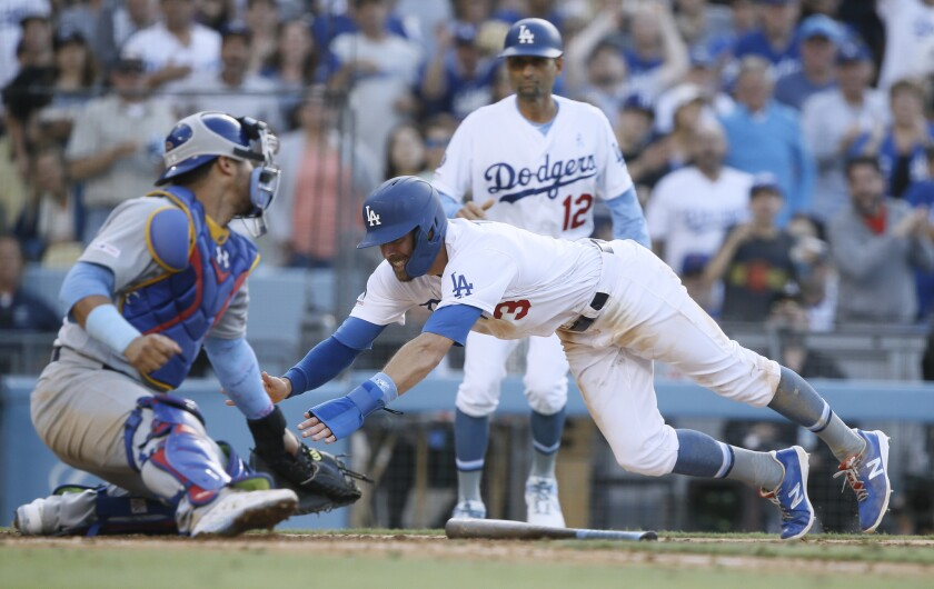 Los Angeles Dodgers' Chris Taylor, center, slides away from the tag by Chicago Cubs catcher Willson