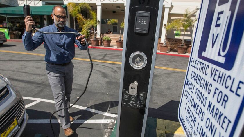 Sri Rao of Los Angeles unplugs his electric car after charging it while shopping at a Whole Foods Market on March 15.