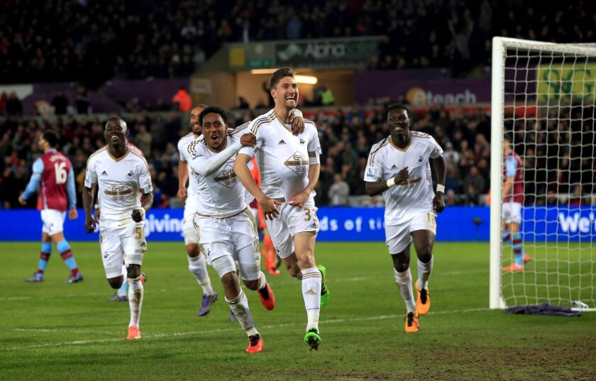 Swansea City's Federico Fernandez, second right, celebrates scoring his side's first goal of the game during their English Premier League soccer match against Aston Villa at the Liberty Stadium, Swansea, Wales, Saturday, March 19, 2016. (Nick Potts/PA via AP) UNITED KINGDOM OUT - NO SALES - NO ARCHIVES