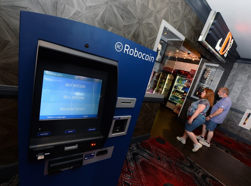 Guests walk by a newly installed Robocoin ATM that accepts bitcoins in Las Vegas.