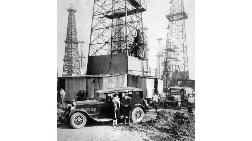 February 1928: Mr. and Mrs. A. W. Cleaver with their new car in front of oil wells on their Seal Beach land.