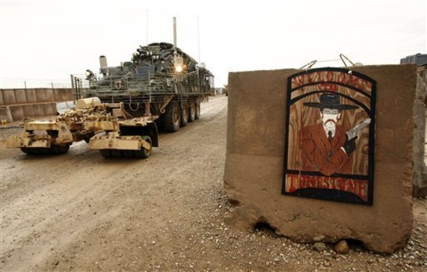 A U.S. Stryker armored vehicle leaves the Tombstone base in the Helmand province, Southern Afghanistan, Sunday, Feb. 7, 2010. The sign at the entrance shows Wyatt Earp, the legendary lawman of the American Wild West. (AP Photo/Pier Paolo Cito)