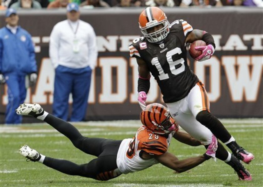 Cleveland Browns wide receiver Josh Cribbs (16) runs past Cincinnati Bengals cornerback Leon Hall for a first down in the second quarter of an NFL football game Sunday, Oct. 3, 2010, in Cleveland. (AP Photo/Tony Dejak)