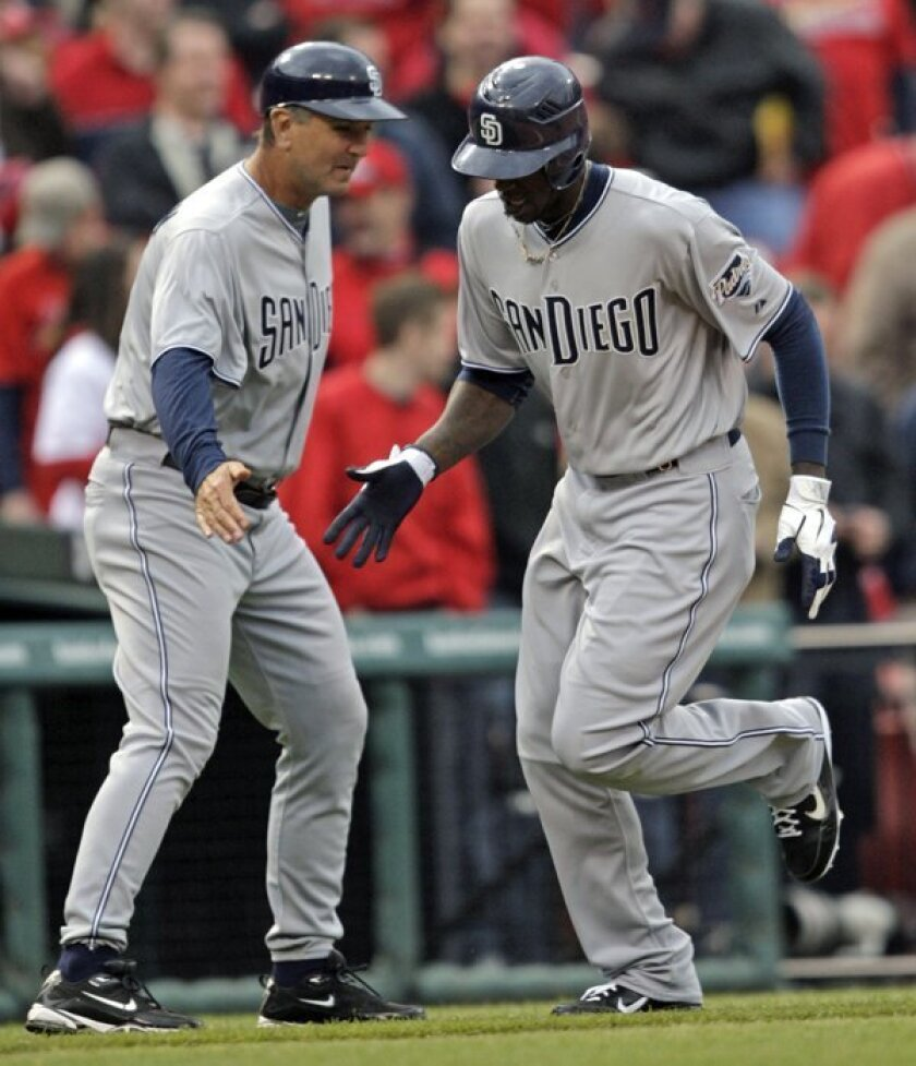 Cameron Maybin celebrates with third-base coach Glenn Hoffman during the ninth inning of a baseball game against the St. Louis Cardinals on Thursday, March 31, 2011, in St. Louis. The Padres beat the Cardinals 5-3 in 11 innings.