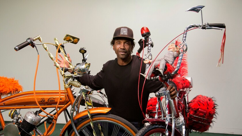 Skid Row artist and activist General Dogon posing with his custom bikes at the Los Angeles Poverty Department's Skid Row History Museum and Archive.
