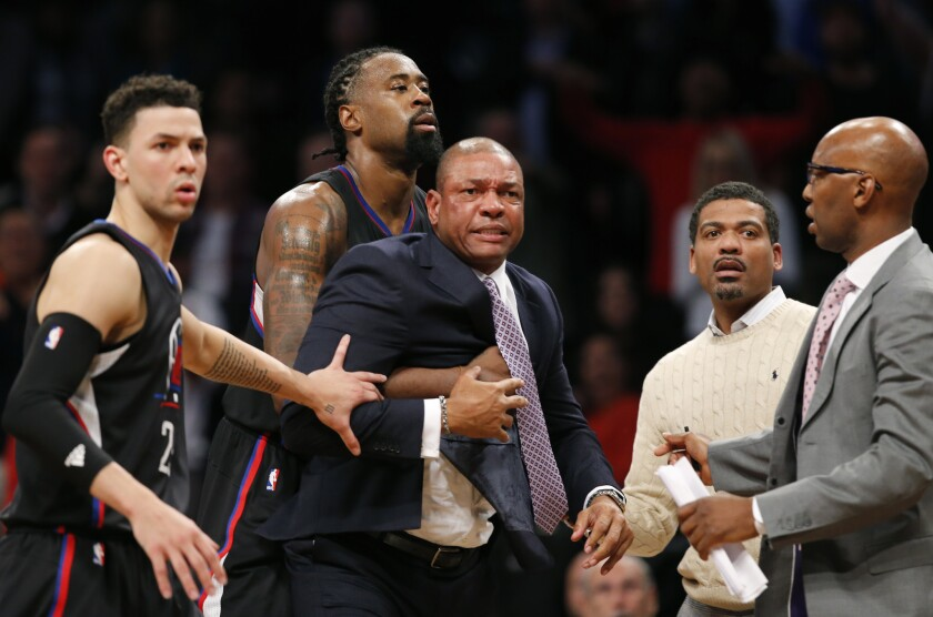 Clippers guard Austin Rivers, left, center DeAndre Jordan and others move to restrain Coach Doc Rivers during an argument about a referee's call Tuesday night against Brooklyn.