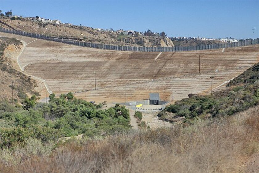 An estimated 1.5'million cubic yards of earth fill most of the canyon  known as Smuggler's Gulch near the international border. A secondary  fence of steel mesh lines the berm. (John R. McCutchen / Union-Tribune)