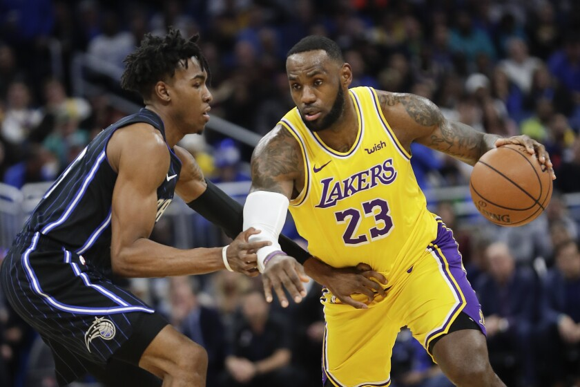 Los Angeles Lakers' LeBron James (23) drives around Orlando Magic's Wes Iwundu, left, during the first half of an NBA basketball game, Wednesday, Dec. 11, 2019, in Orlando, Fla. (AP Photo/John Raoux)