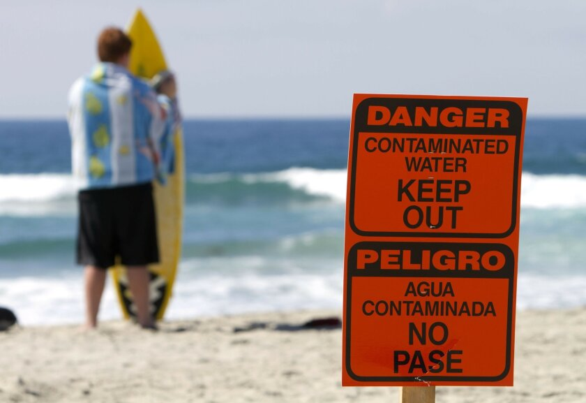 With a sign warning people about contaminated water from a sewage spill in the Batiquitos Lagoon in the foreground, surfer Will Fox, 13, looks at the ocean after surfing at Ponto Beach in Carlsbad on Monday. An estimated 9,000 gallons of sewage spilled into the lagoon in Carlsbad around 8 am Monday. HAYNE PALMOUR IV / UT