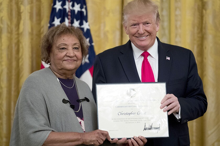 President Trump presents a Certificate of Commendation to Minnie Grant, the mother of Christopher Grant, during a ceremony at the White House on Monday.