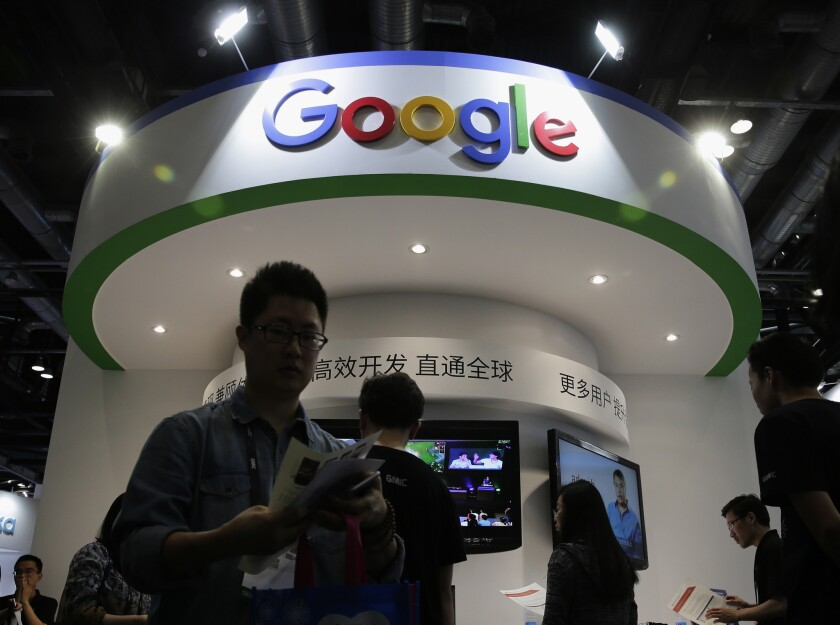 In this April 28, 2016, photo, visitors gather at a display booth for Google at the 2016 Global Mobile Internet Conference in Beijing. Google employees are upset with the company's secretive plan to build a search engine that would comply with Chinese censorship.