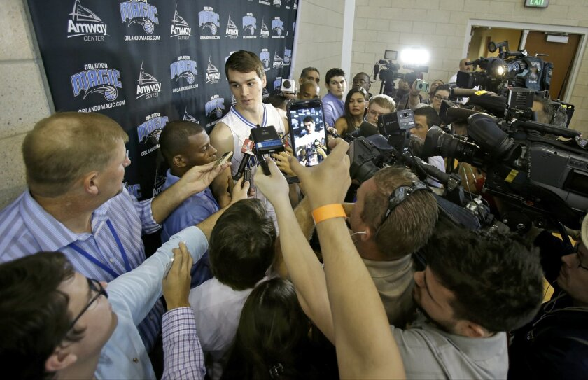 Orlando Magic forward Mario Hezonja, center left. is surrounded by media as he answers questions during the basketball teams NBA media day, Friday, Sept. 25, 2015, in Orlando, Fla. (AP Photo/John Raoux)