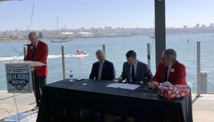 Officials from the San Diego County Credit Union Holiday Bowl are joined by representatives from the Pac-12 and ACC conferences Thursday at a harborside restaurant to announce an agreement for the new bowl cycle. Santa Claus rides off in the background on a jet ski after delivering the new six-year bowl contract.