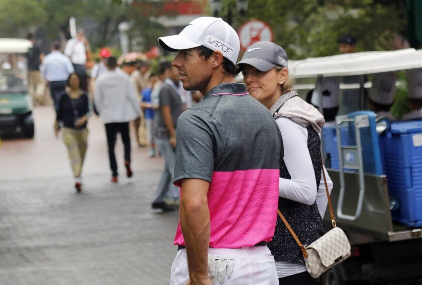 Rory McIlroy of Northern Ireland, left, walks back to the clubhouse due to the bad weather warning during the third round of the HSBC Champions golf tournament at the Sheshan International Golf Club in Shanghai, China Saturday, Nov. 7, 2015. (AP Photo)