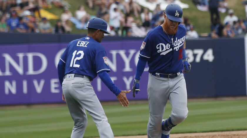 The Dodgers' Justin Turner, shown here Thursday with third base coach Dino Ebel, has been swinging a hot bat in spring training.
