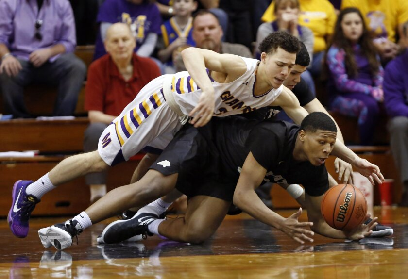 Marion's Tim Leavell, top, and Griffith's Cornell Hampton dive for a loose ball in the Class 3A semi-state basketball game, Wednesday, March 23, 2016, in Lafayette, Ind. The game was pushed back to Wednesday after the bus carrying the Griffith basketball team was involved in an accident on the way to Lafayette last Saturday. (John Terhune/Journal & Courier via AP) MANDATORY CREDIT; NO SALES; TV OUT; RADIO OUT; LOCAL INTERNET OUT
