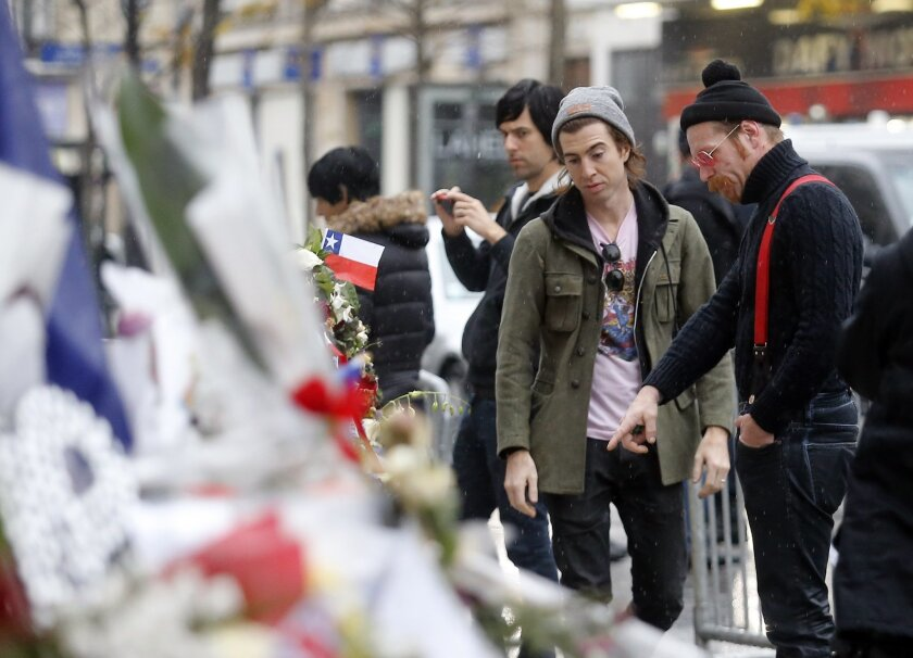FILE - In this Dec. 8, 2015 file photo, members of the band Eagles of Death Metal, Jesse Hughes, right, and Julian Dorio pay their respects to 89 victims who died in a Nov. 13 attack at the Bataclan concert hall in Paris, France. The Eagles of Death Metal band is scheduled to play at the Olympia Th