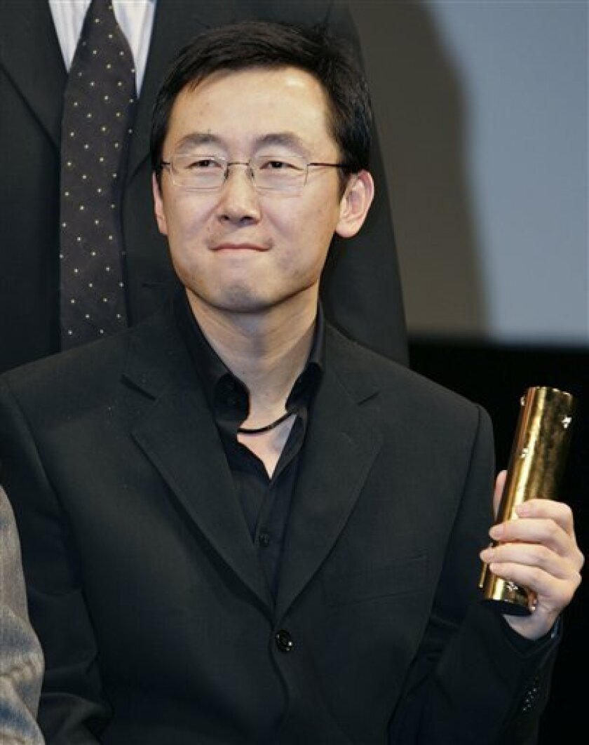 """FILE -- In this Oct. 31, 2004 file photo, Chinese director Lu Chuan holds his Special Jury Prize which he won for his film """"Kekexili: Mountain Patrol"""" during the awarding ceremony of the 17th Tokyo International Film Festival in Tokyo. The Chinese director whose movie was pulled from an American film festival to protest a documentary about the Dalai Lama said Thursday, Jan. 7, 2010, he accepted the decision _ but hinted he was under pressure to toe the government line. The Palm Springs International Film Festival said in a statement posted on its Web site Wednesday that Chinese film authorities pulled Lu Chuan's """"City of Life and Death"""" and the comedy """"Quick, Quick, Slow"""" from the event. Organizers said the Chinese acted after they refused to drop the documentary """"The Sun Behind the Clouds: Tibet's Struggle for Freedom"""" at the request of the Chinese government. (AP Photo/Shizuo Kambayashi, File)"""