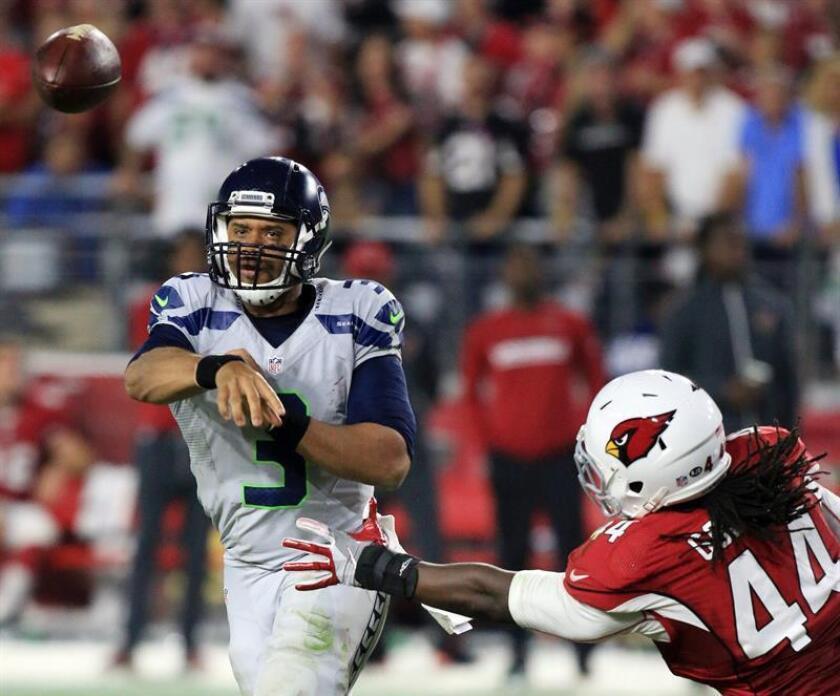 El quarterback de los Seattle Seahawks Russell Wilson (i) protege el balón en una carrera. EFE/Archivo