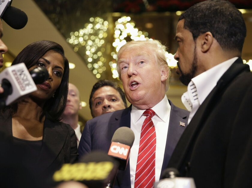 Republican Presidential candidate Donald Trump, center, talks with reporters while surrounded by a group of African-American religious leaders in New York, Monday, Nov. 30, 2015. Trump met with a coalition of 100 African-American evangelical pastors and religious leaders in a private meeting at Trump Tower. (AP Photo/Seth Wenig)