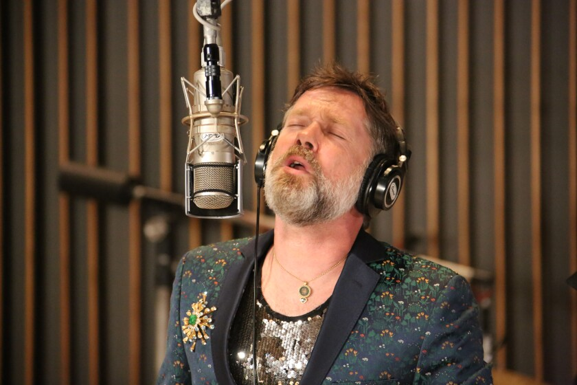 A bearded man in a floral jacket and sequined shirt sings into a suspended microphone.