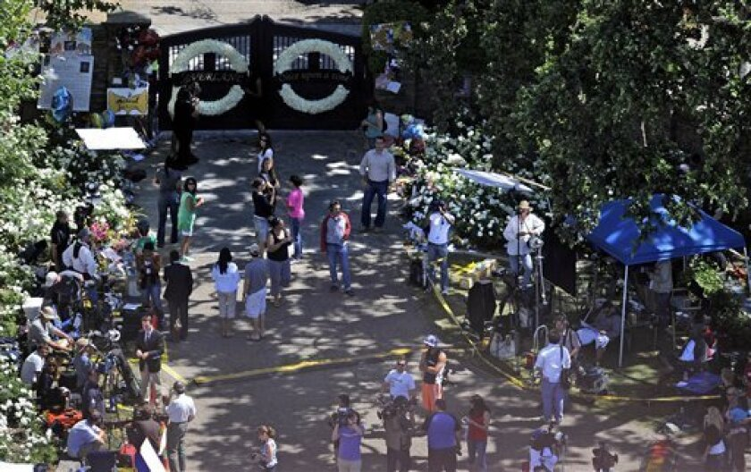 Members of the news media stand in front of the main gate to Neverland Ranch in Los Olivos, Calif., Wednesday, July 1, 2009 as preparations are made for a memorial service for the late pop star Michael Jackson at his former residence. (AP Photo/Chris Carlson)