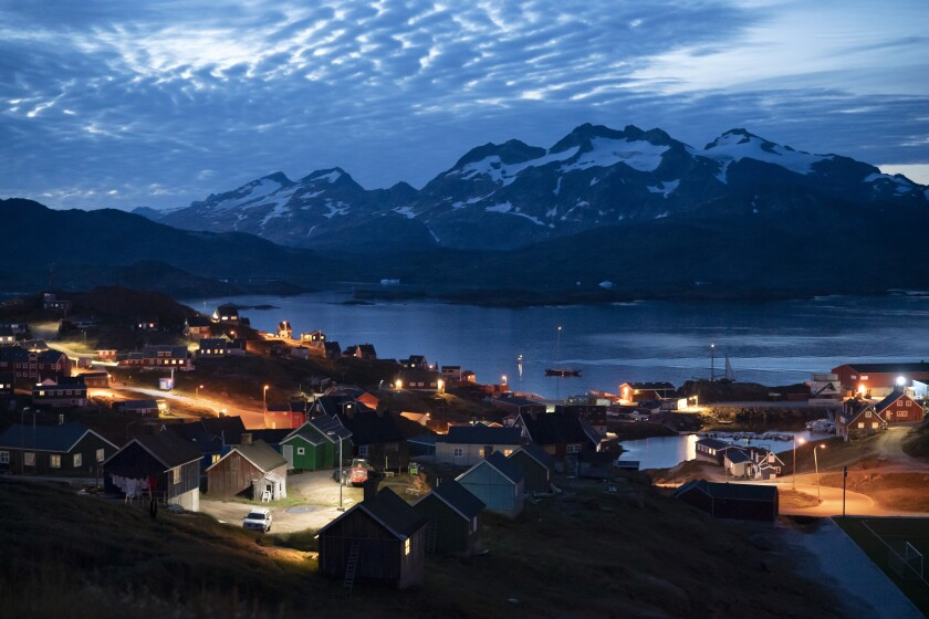 Homes are illuminated after the sunset in Tasiilaq, Greenland, Aug. 16, 2019