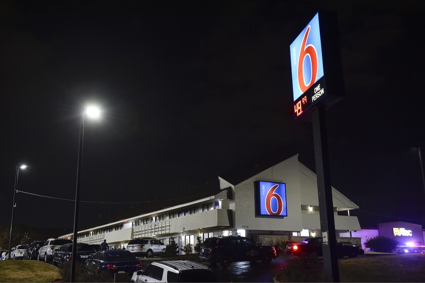 """In this Monday Nov. 18, 2019 photo, police surround a motel parking lot in Kansas City, Missouri where a Clay County deputy fatally shot a man after an altercation during a car check. The deputy was conducting the check Monday afternoon when he and the driver got into a fight outside a Motel 6 near the Worlds of Fun amusement park. Kansas City police say that's when the deputy was """"forced into using lethal force."""" Police found suspicious devices in the back seat of the vehicle, but determined they weren't explosives. (Jill Toyoshiba/The Kansas City Star via AP)"""